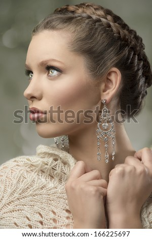 close-up portrait of charming woman with splendid eyes, elegant hair-style, precious earrings and wool shawl    - stock photo