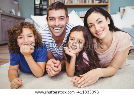 Close-up portrait of cheerful family lying on carpet at home - stock photo