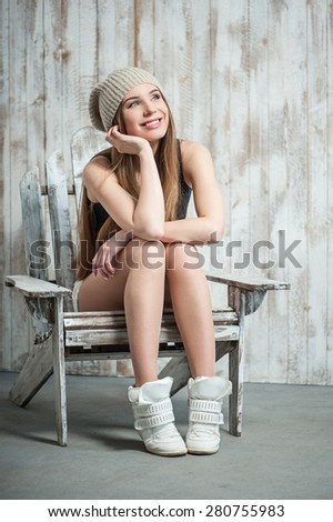 Close up portrait of cheerful hipster girl with cool woven hat, who is sitting on the chair dreamily smiling and looking towards, her hand is propping up her head. - stock photo