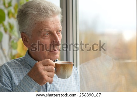 Close-up portrait of cheerful mature man at home with tea - stock photo