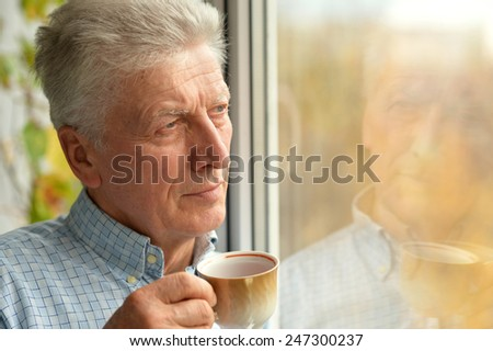 Close-up portrait of cheerful mature man drinkig tea at home - stock photo