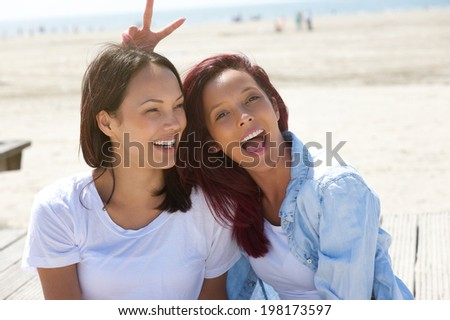 Close up portrait of cheerful sisters having fun at the beach - stock photo