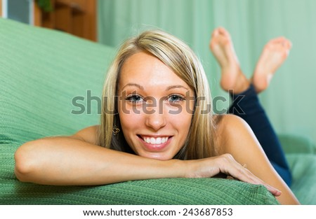Close-up portrait of cheerful smiling blonde girl with blue eyes at home  - stock photo