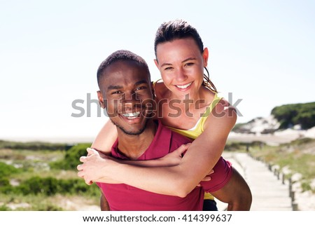 Close up portrait of cheerful young couple enjoying summer, man piggybacking his girlfriend outdoors. - stock photo