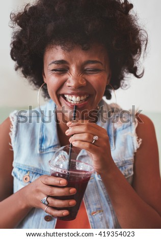 Close up portrait of cheerful young woman drinking fresh fruit juice and smiling. Happy young african female model having a drink. - stock photo