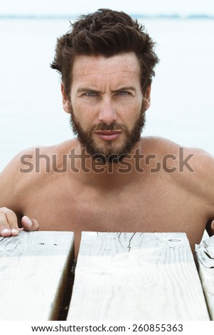 Close up Portrait of Confident Athletic Handsome Man with No Shirt Posing at the Sea  - stock photo