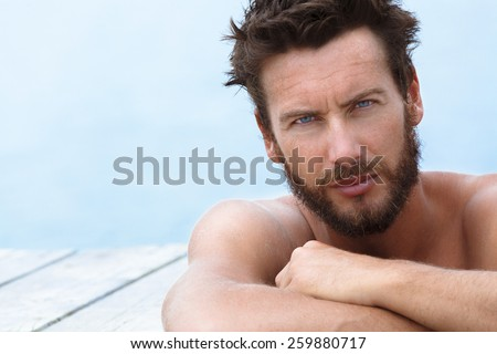 Close up Portrait of Confident Gorgeous Handsome Man with No Shirt Posing at the Sea  - stock photo