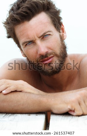 Close up Portrait of Confident Seductive Handsome Man with No Shirt Posing at the Sea  - stock photo