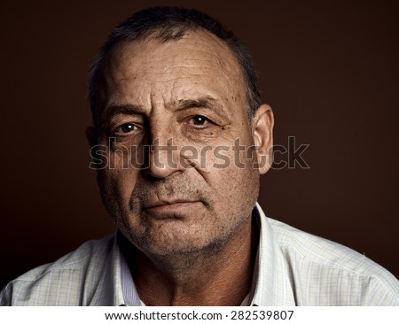 Close-up portrait of contemplative senior caucasian sad man thinking about something and looking at camera. - stock photo