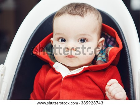 Close-up portrait of cute adorable Caucasian little baby boy with dark black eyes sitting in high chair indoors looking in camera - stock photo
