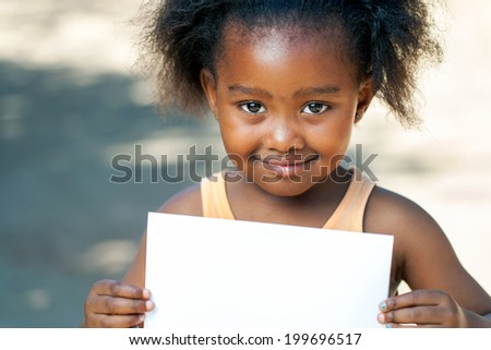 Close up portrait of cute African girl holding blank white card outdoors. - stock photo