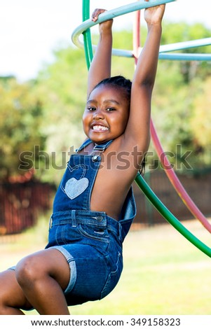 Close up portrait of cute African girl playing in park. - stock photo