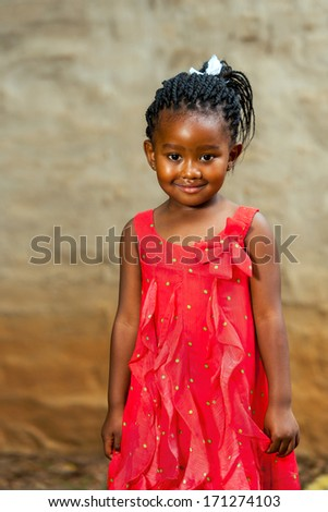 Close up portrait of cute african girl standing in red dress outdoors.  - stock photo
