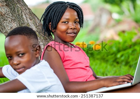 Close up portrait of cute African girl typing on laptop next to brother under tree in park. - stock photo