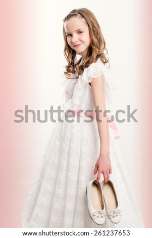 Close up portrait of cute Communion girl holding shoes. - stock photo