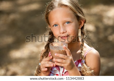 Close up portrait of cute girl drinking milk chocolate outdoors. - stock photo