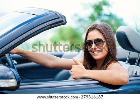 Close up portrait of Cute girl driving convertible doing thumbs up. - stock photo