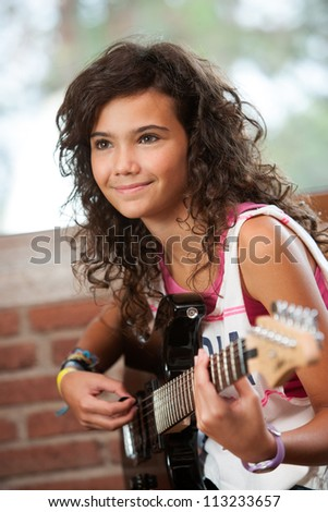 Close up portrait of cute girl playing guitar indoors. - stock photo