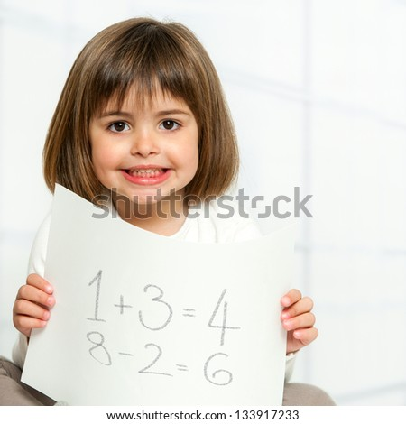 Close up portrait of cute girl showing maths equations on paper. - stock photo