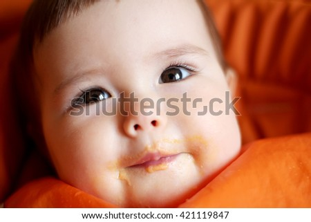 Close-up portrait of cute little baby girl in the bib dirty with her first food, indoor portrait, health nutrition concept - stock photo