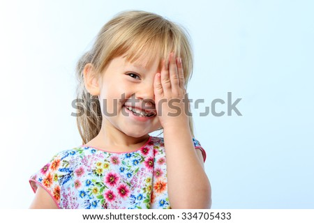 Close up portrait of Cute little girl closing one eye with hand against blue background. - stock photo