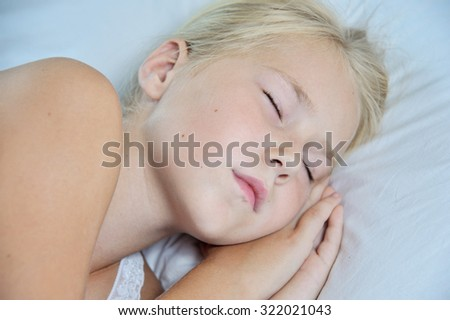 Close up portrait of cute little girl sleeping in her bed at home - stock photo