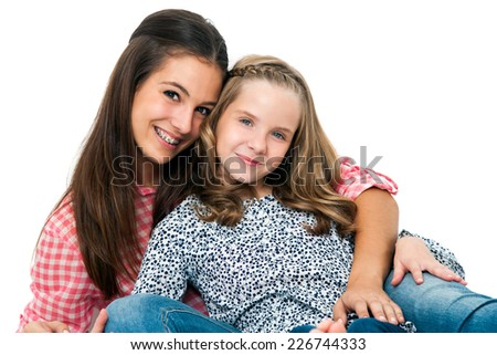 Close up Portrait of cute teen girl with younger sister.Isolated on white background. - stock photo