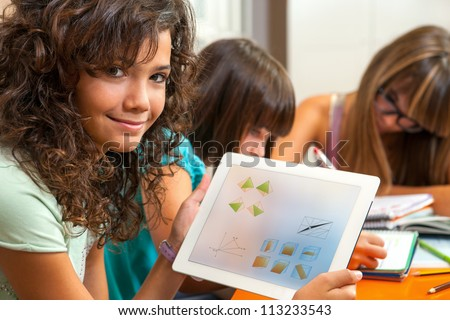 Close up portrait of cute young student holding tablet with homework. - stock photo