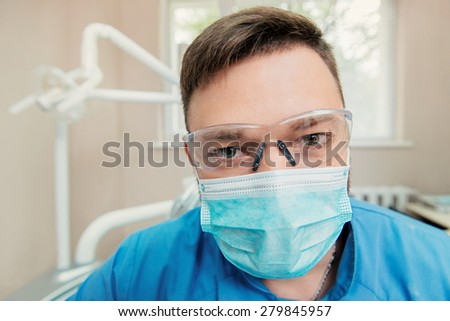 Close-up portrait of dentist with sterile mask and glasses - stock photo