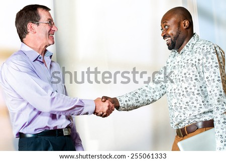 Close up portrait of diverse business partners shaking hands on agreement. - stock photo