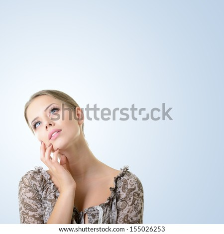 Close-up portrait of dreaming girl, isolated over blue background with copyspace - stock photo