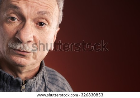 Close-up portrait of elderly man with a surprised expression on red background with copy-space - stock photo