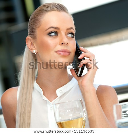 Close up portrait of elegant businesswoman talking on smart phone during lunch. - stock photo
