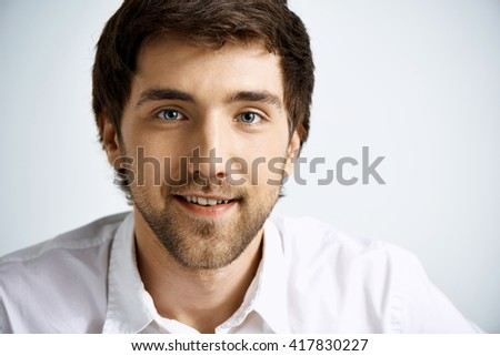 Close up portrait of elegant confident handsome young businessman in white shirt looking at camera smiling. Studio, isolated on grey background. - stock photo