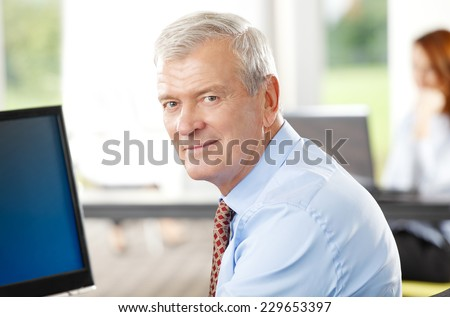 Close-up portrait of executive senior businessman sitting at office while using computer. Business people. - stock photo