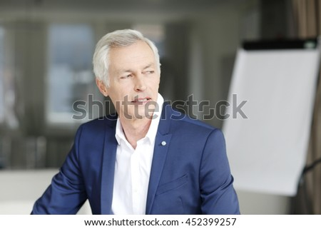 Close-up portrait of executive senior director sitting at office. - stock photo