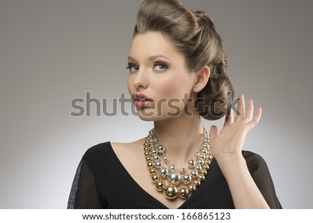 close-up portrait of fashion pretty girl with brown elegant hair-style and bright big necklace.  - stock photo