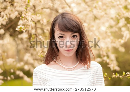 Close-up portrait of fashionable brunette girl with beautiful brown eyes.Cherry blossoms on a background - stock photo
