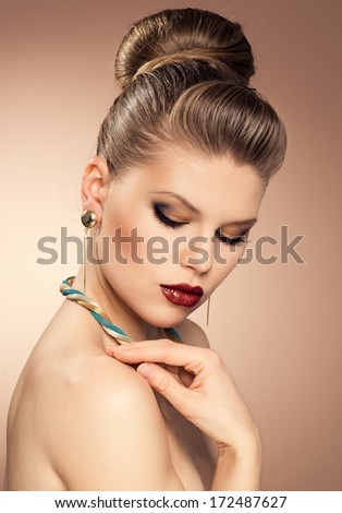 Close-up portrait of fashionable lady wearing luxury golden jewelery with professional make-up and beautiful hairstyle. Young attractive Caucasian woman model posing in studio.  - stock photo