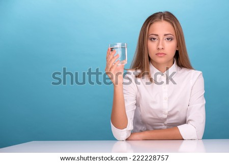 Close-up portrait of female scientist in overall holding in her hands four tubes with some substances in laboratory doing some experiments isolated on blue background, with selective focus on a tubes - stock photo