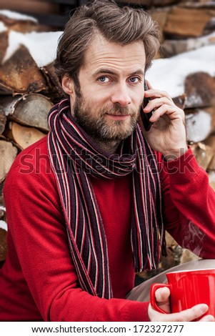 Close up portrait of forty years old caucasian man talking on a mobile phone while drinking hot tea outdoor - winter countryside landscape - stock photo