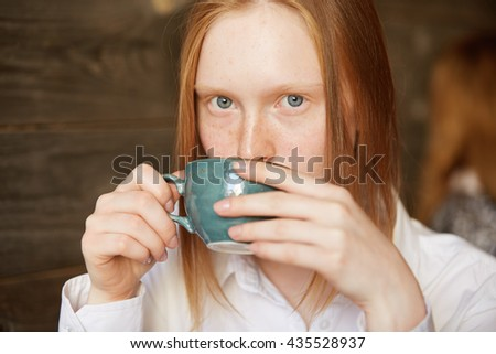 Close up portrait of freckled teenage girl holding a cup of tea or coffee, looking at the camera. Young redhead female office worker in formal shirt enjoying morning cappuccino before going to work - stock photo