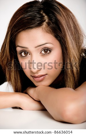 Close-up portrait of fresh, beautiful young Asian Indian model, head resting on arms and desk. - stock photo