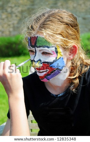 close-up portrait of girl having face painted - stock photo
