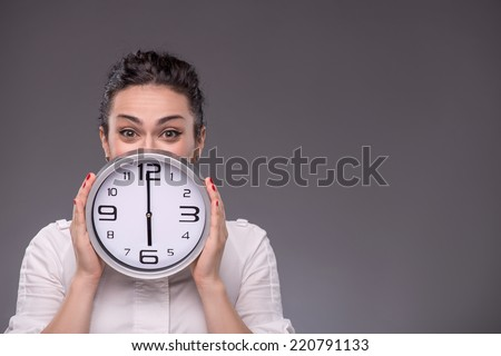 Close-up portrait of girl hiding her face with a big clock in her hands and looking at the camera, isolated on grey background with copy place concept of time management - stock photo