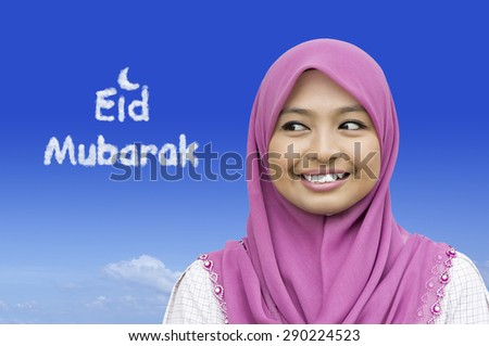 Close-up portrait of girl looking at the Eid Mubarak word in blue sky - stock photo
