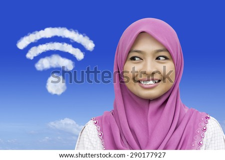 Close-up portrait of girl looking to full coverage of wireless network icon in blue sky - stock photo