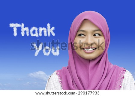 Close-up portrait of girl looking to thank you word in blue sky - stock photo