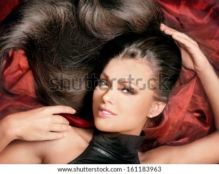 Close-up portrait of glamorous young woman with long hair on red glossy cloth - stock photo