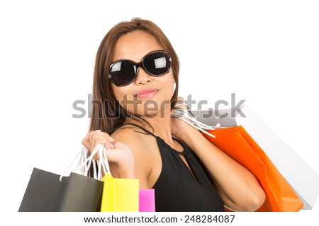 Close up portrait of gorgeous Asian female shopper in sunglasses, black dress holding colorful department store bags over both shoulders, head tilted facing camera. Thai national of Chinese origin - stock photo